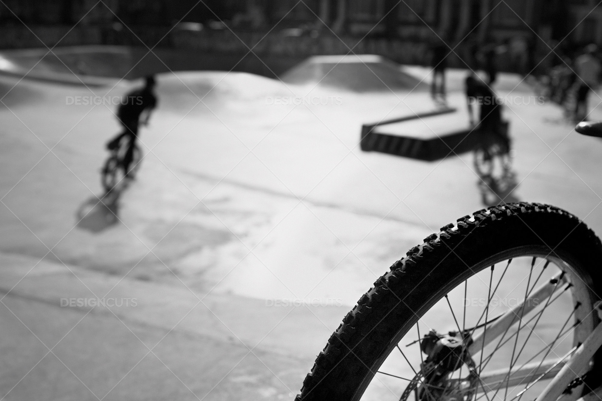 Bike Wheel With Skatepark Out Of Focus In Background