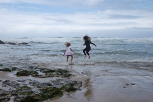 Two Children Play On Shore Of Stormy Beach