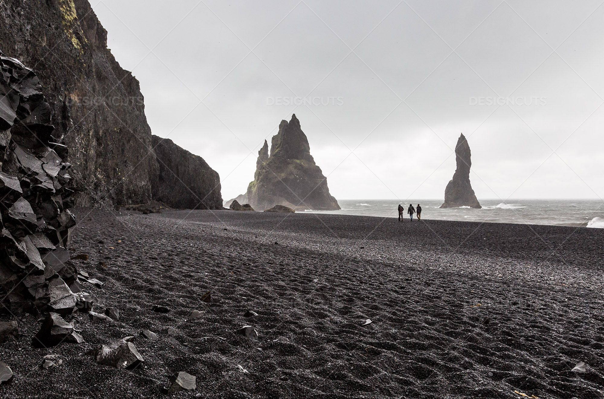 3 People Silhouetted Against The Horizon Walking Along Vík's Black Sand Beach