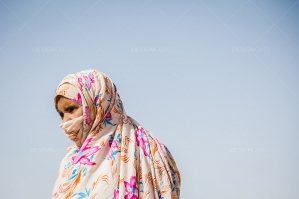 A Sahrawi Woman Wearing A Traditional Dress Against A Blue Sky