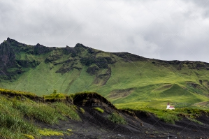 A White Church Amidst Towering Green Hills On The Black Sand Dunes In Vík, Iceland