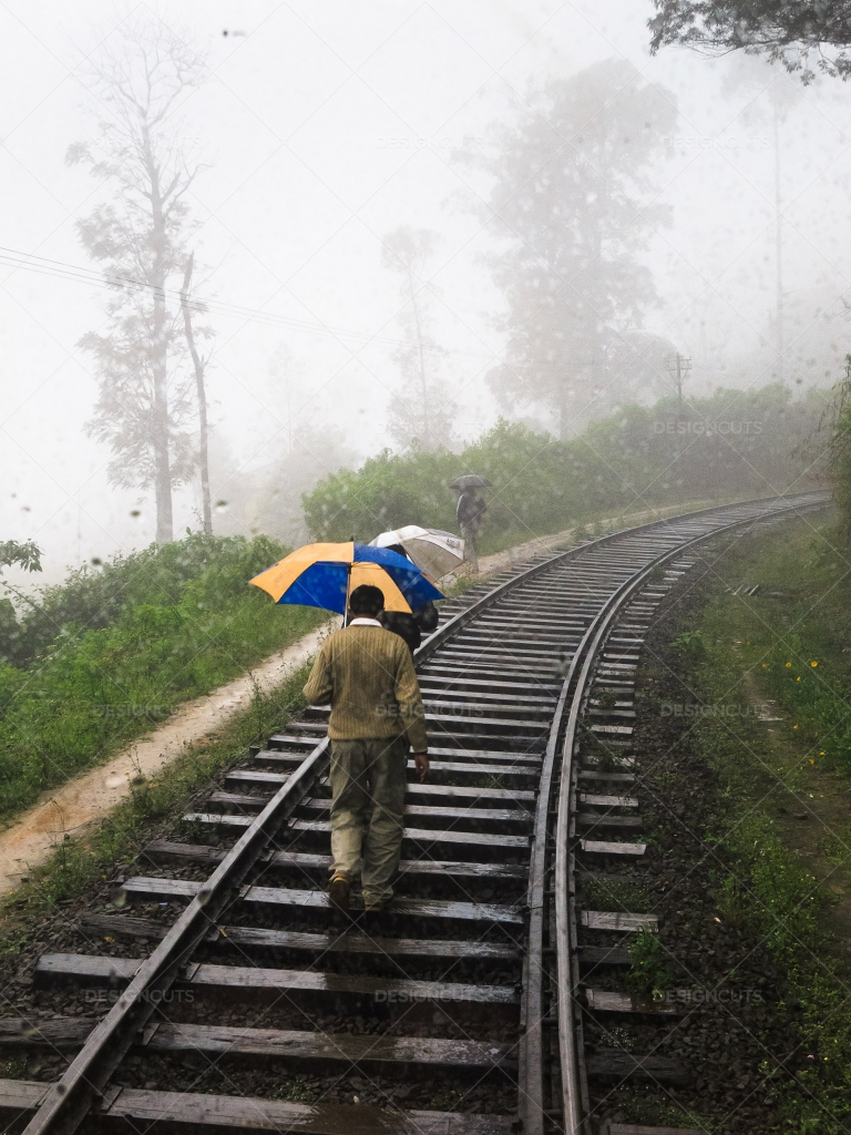 Men-Walking-With-Umbrellas-Along-Train-Tracks-In-The-Rain-Sri-Lanka-Emma-Brown