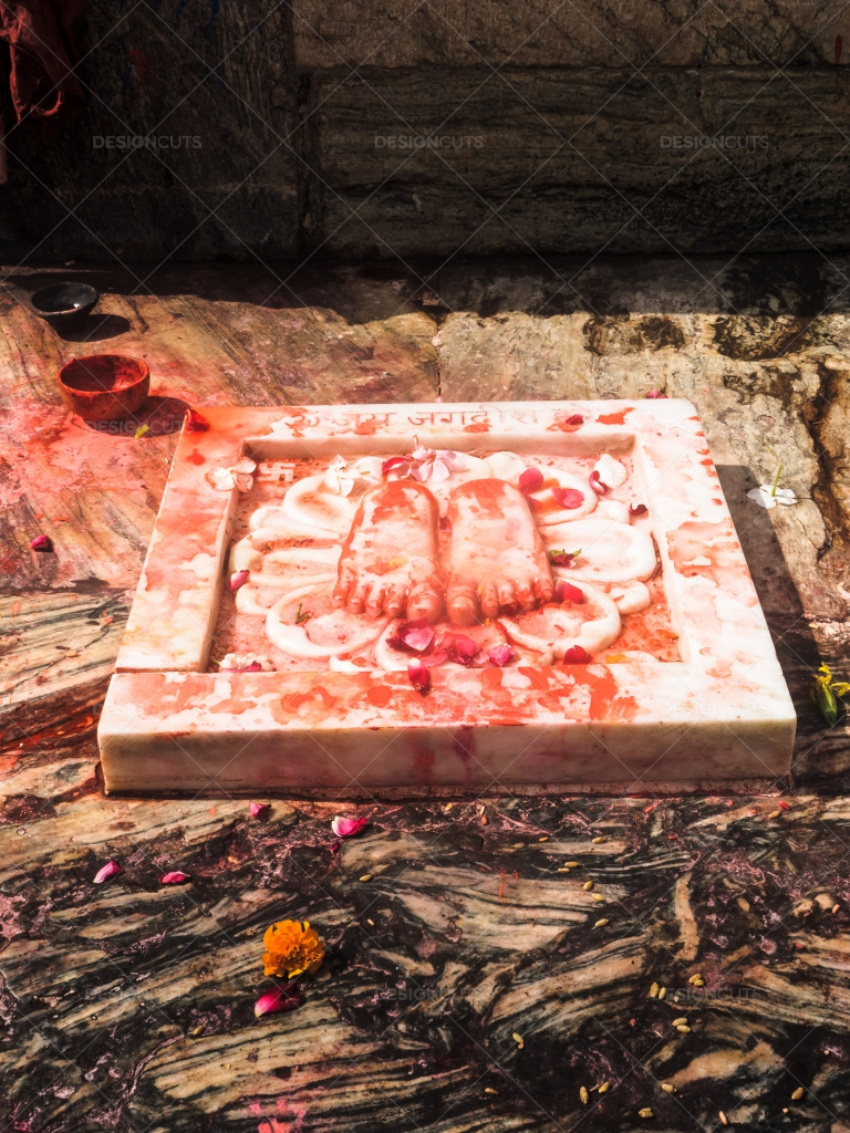 Offerings-Of-Flowers-Next-To-A-Marble=Sculptur-Of-Buddhas-Feet-Emma-Brown
