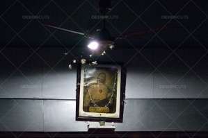 Moths Flying Around A Ceiling Light In Front Of A Painting Of Jesus