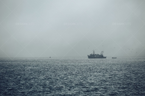 A Misty View Of A Fishing Boat Returning To Harbor