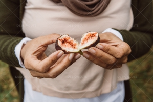 Woman Holding Two Halves Of A Fig In Her Hands